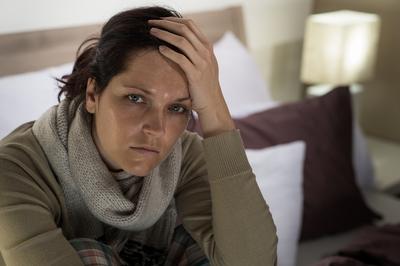 Eine Frau, die sichtlich erkrankt ist, steht für finanziellen Schutz bei Diagnose Krebs bei Mehrwertfinance.