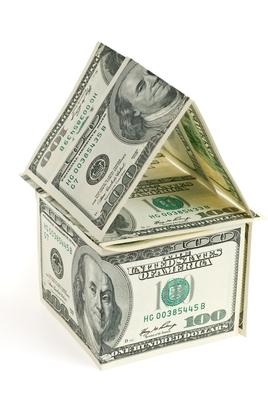 Ein Kartenhaus aus Dollarnoten symbolisiert Immobilienfinanzierung durch Mehrwertfinance.